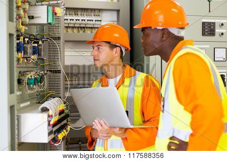 experienced multiracial industrial technicians checking transformer