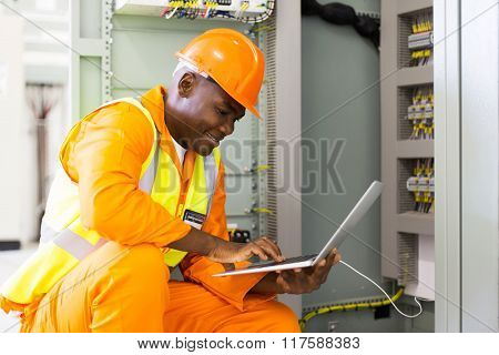 young african american engineer using laptop in machine control room