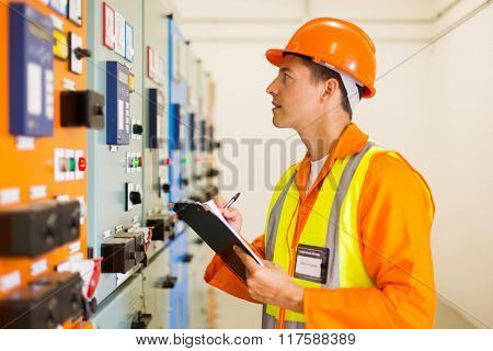 engineer writing results of measurements in power plant control room