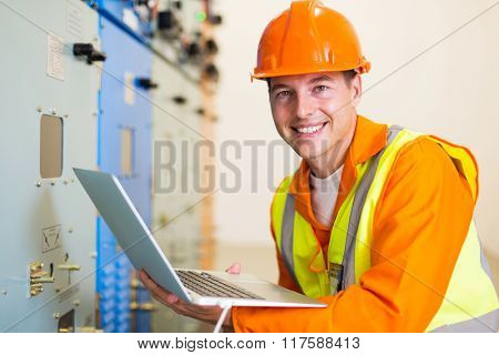 electrical worker with laptop computer in control room