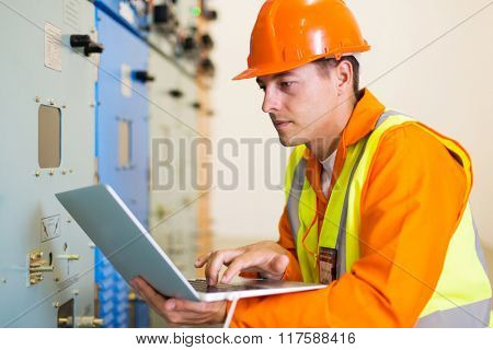 electrical engineer using laptop in power plant control room