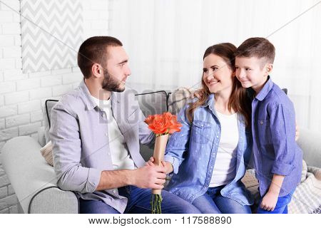 Husband and son giving roses to wife