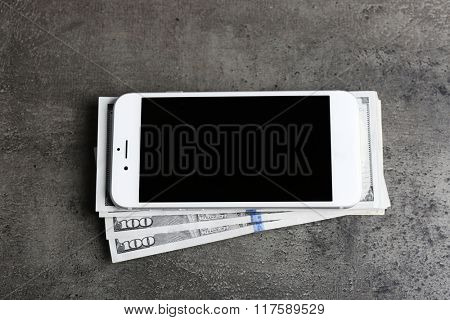 Mobile phone and money on grey background. Concept of payment and savings.