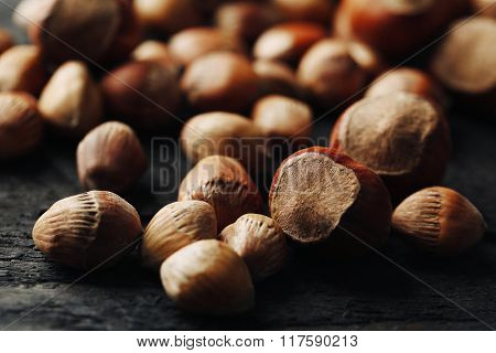Scattered hazelnuts and acorns on grey wooden table, close-up