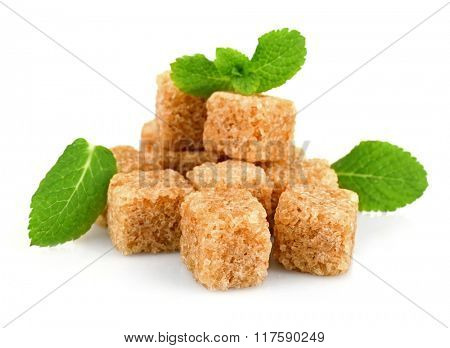 Pile of brown sugar cubes and stevia isolated on white background