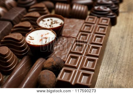 Delicious chocolate candies on wooden background