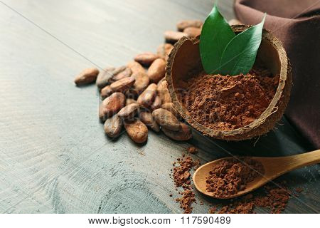 Bowl with aromatic cocoa powder and green leaf on wooden background, close up