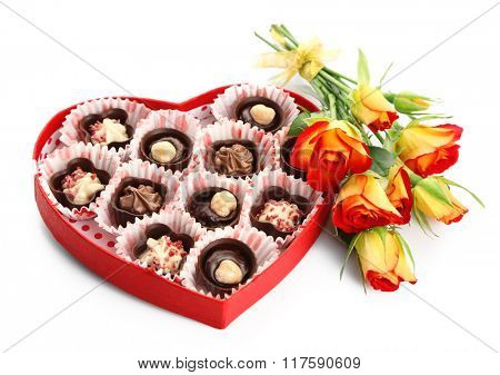 Heart shaped box with candies and flowers, isolated on white