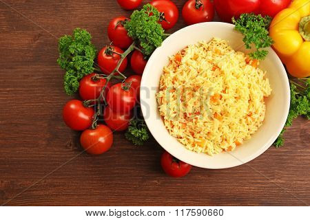 Stewed rice with a carrot on a plate over wooden background