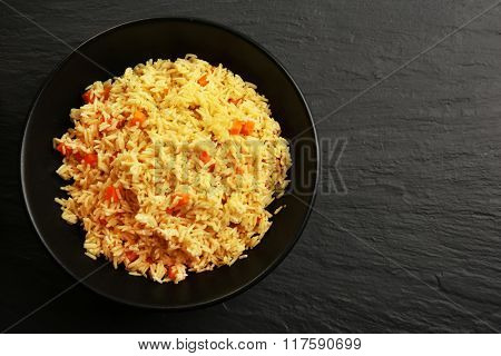 Stewed rice with a carrot on a plate over black background, close up