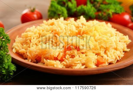 Stewed rice with a carrot on a brown plate over wooden background, close up
