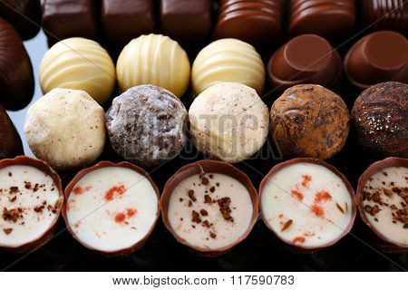 Assorted chocolate candies on black background, close up