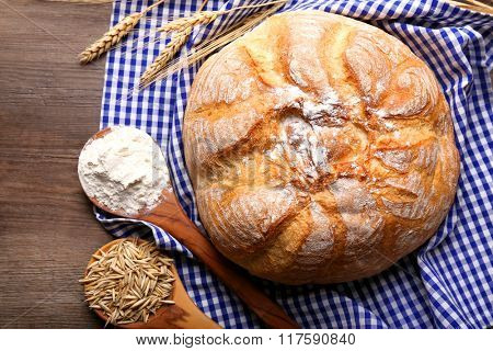 Fresh baked bread, flour, wheat in spoons and napkin on the table, close-up