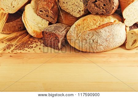 Assortment of fresh baked bread on the wooden background