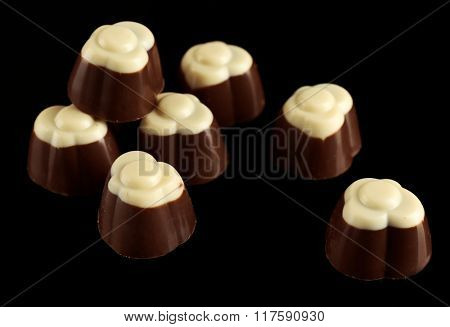 Assorted chocolate candies on black background