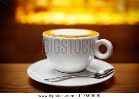 Cup of coffee on the table in the cafe, close up