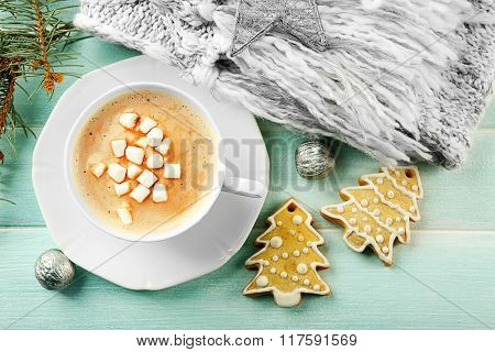Cup of hot cacao with marshmallow, cookies and warm scarf on blue table