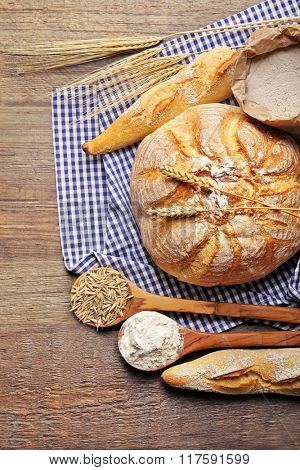 Fresh baked bread, flour, wheat in spoons and napkin on the wooden background