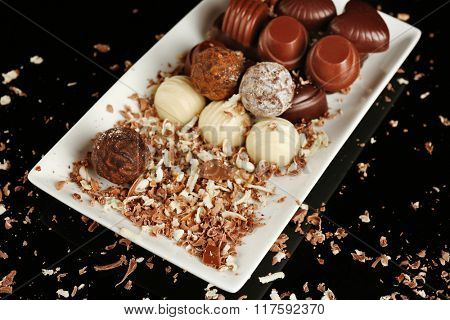 Assorted chocolate candies on white plate with flakes over black background