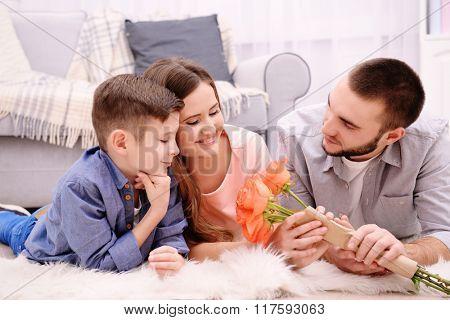 Happy family lying on carpet beside sofa in the room