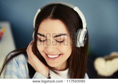 Happy young woman with headphones listening to music at home