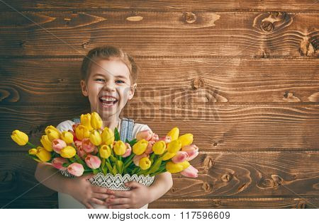 Cute child girl with a bouquet of tulips. Mothers day, spring concept.