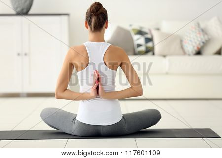 Health concept. Young beautiful woman does yoga exercise in the modern room