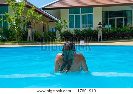 Woman relaxing in blue outdoor swimming pool