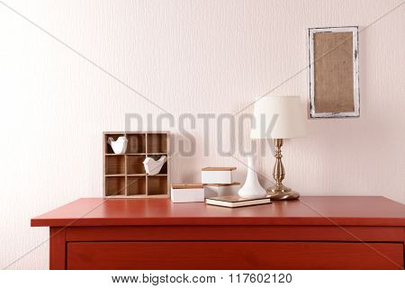 Room interior with red wooden commode, frame and lamp on light wall background