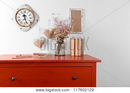 Room interior with red wooden commode, books and clock on light wall background