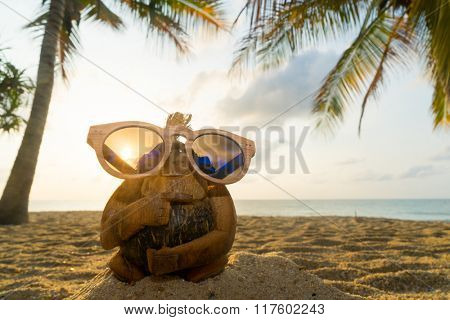 Coconut monkey with sunglasses  at the beach.