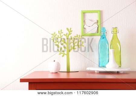 Room interior with red wooden commode and glass bottles on light wall background