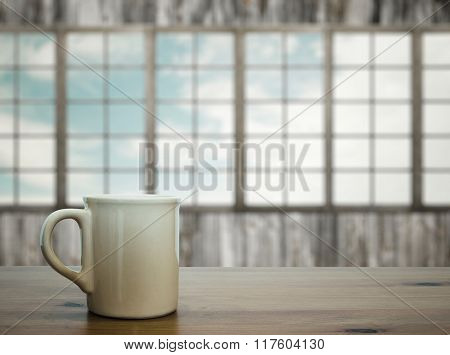 mug on wooden table in old room with big windows