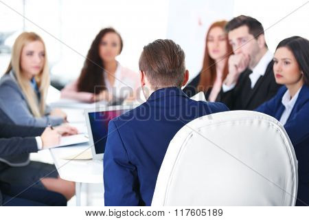 Young businessman sitting back in front of colleagues in the office