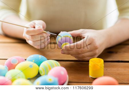 easter, holidays, tradition and people concept - close up of woman hands coloring easter eggs with colors and brush