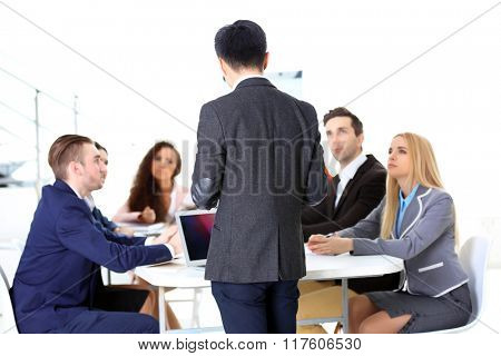 Young businessman standing back in front of colleagues in the office