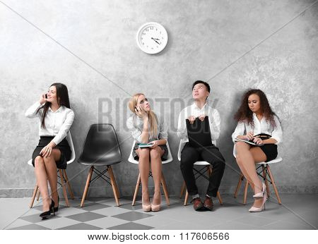 Young people sitting on a chairs in grey hall
