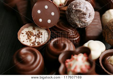 Delicious chocolate candies on wooden background, close up