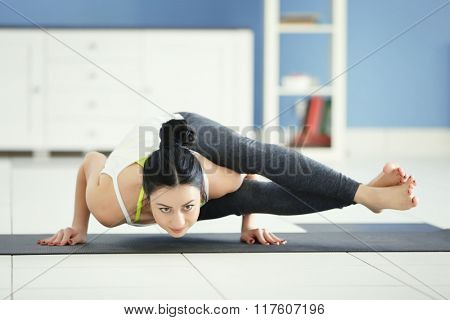 Health concept. Young attractive woman does yoga exercise in the room