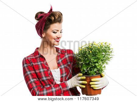 Woman with pin-up hairstyle holding flower pot with yellow daisi
