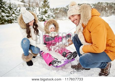 parenthood, fashion, season and people concept - happy family with child on sled having fun outdoors