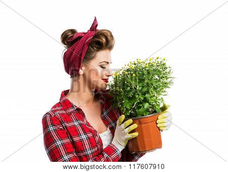 Woman with pin-up hairstyle smelling yellow daisies in flower po