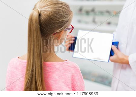 health care, people, eyesight and vision concept - close up of optician with mirror helping little girl to choose glasses at optics store