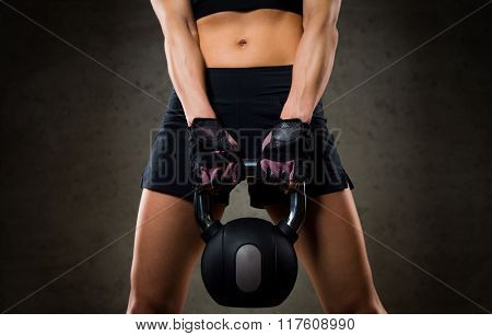 fitness, sport, exercising, weightlifting and people concept - close up of young woman flexing muscles with kettlebell in gym