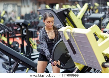 fitness, sport, bodybuilding, exercising and people concept - young woman adjusting leg press machine in gym