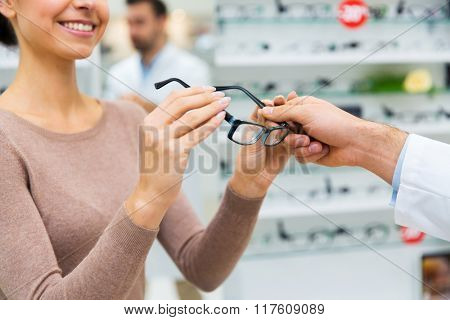 health care, people, eyesight and vision concept - close up of woman taking glasses from optician hand at optics store