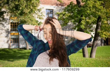 school, education, people and teens concept - happy pretty teenage student girl holding to head over summer campus background