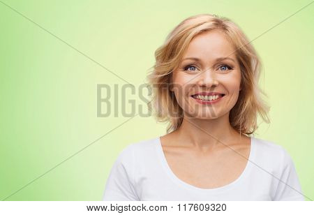 happiness and people concept - smiling woman in blank white t-shirt over green natural background
