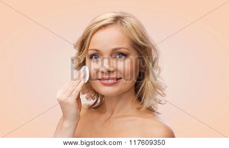 beauty, people and skincare concept - young woman cleaning face and removing make up with cotton pad over beige background
