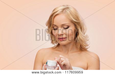 beauty, people, skincare and cosmetics concept - middle aged woman with cream jar over beige background